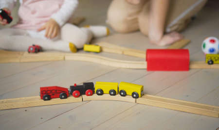 Educational games at home with a child. Games with a constructor. Mom helps her daughter build a railway.