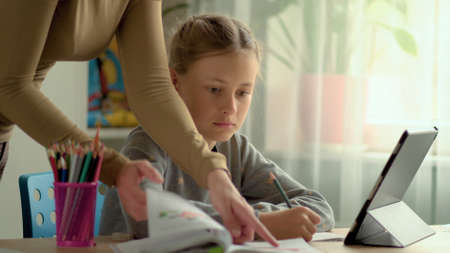 Cute children use laptop for education, online study, home studying, Girl have homework at distance learning. Lifestyle concept for home schooling. Mother helps daughter and son.