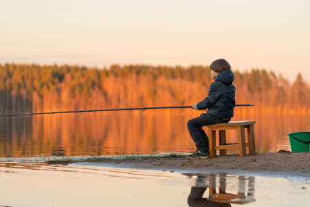 Fishing. Little boy with a fishing rod in his hands on the lake. Against the background of a bright forest in the rays of the setting sun.