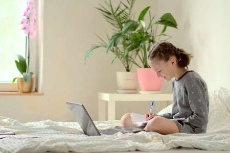 Schoolgirl is doing homework while sitting on the bed at home. Smiling beautiful girl studies online with a laptop and writes in a notebook. Distance learning. Side view.