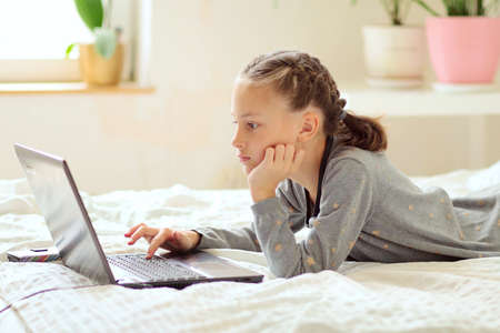 Schoolgirl doing homework lying on the bed at home. In front of the girl is a laptop. Self-education concept. Close-up. Side view. Banco de Imagens