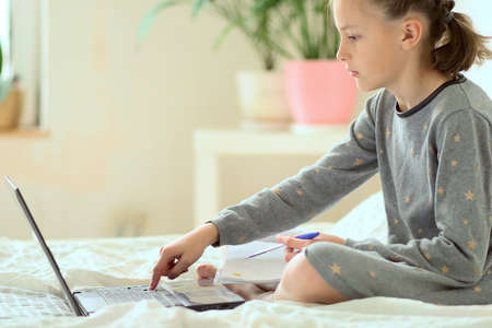 Schoolgirl is doing homework while sitting on the bed at home. Young beautiful girl studies online with a laptop. Distance learning. Close-up. Side view.