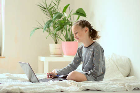 Online training. Additional activities at home. Smiling beautiful girl doing homework while sitting on the bed at home. 免版税图像