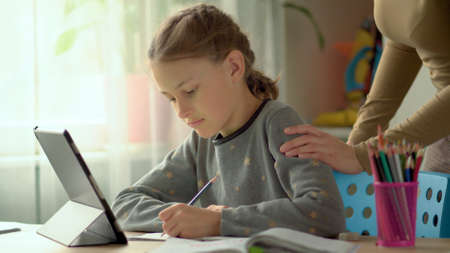 Cute children use laptop for education, online study, home studying. Boy and Girl have homework at distance learning. Concept for home schooling 免版税图像