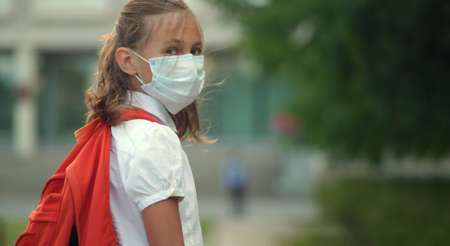 Child goes back to school. Cute pupil with backpack. Girl in safety masks looks at camera