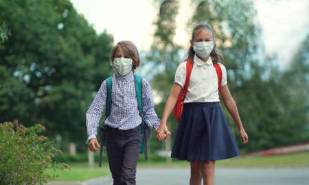 Children go back to school. Cute pupils with backpacks. Boy and girl in safety masks Imagens