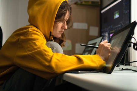 A young female student sitting at the table, using graphics tablet. Woman working from home. Concept for distance learning or home office