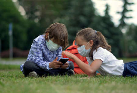 Children go back to school. Cute pupils with backpacks. Boy and girl in safety masks lie on the grass Imagens