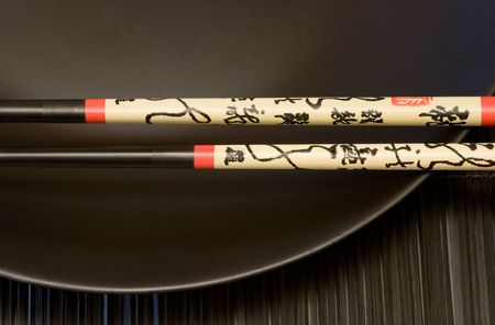 close up of chinese chopsticks with calligraphy and black plate