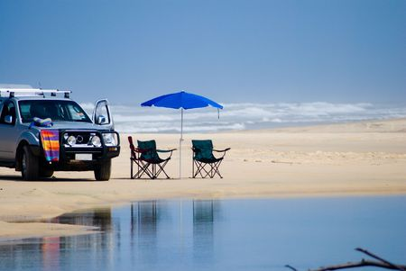 with umbrella and bach-chairs on beach of Fraser Island