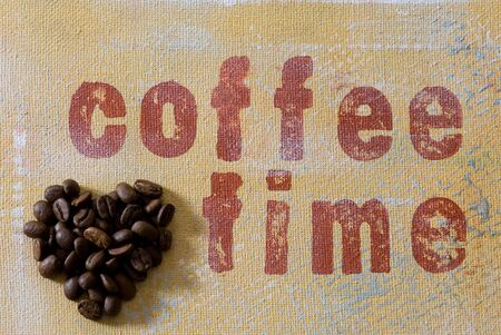 coffeetime: heart made of coffeebeans and handmade background with writing, artwork in the back is created and painted by myself