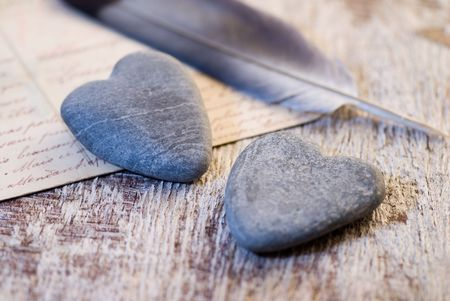 stone hearts and feather on old handwritten letter