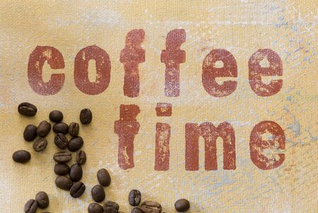 coffeetime: coffee beans on handmade background with writing, artwork in the back is created and painted by myself