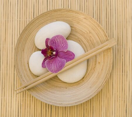 still life with pink orchid flower and white pebble on bamboo plate photo