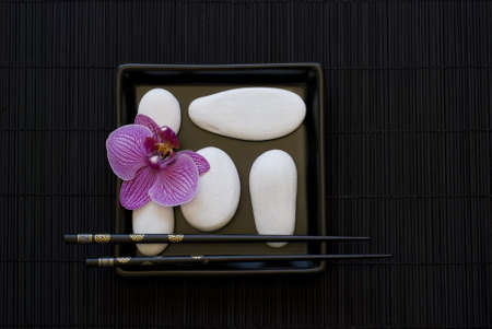 still life with pink orchid flower and white pebble on black plate photo