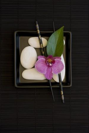 분홍색 난초 꽃과 흰 조약돌 검은 접시에 아직도 인생