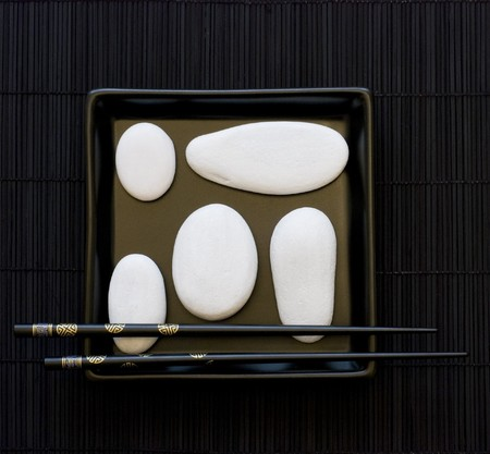 still life of white pebble and black chopsticks on black plate photo