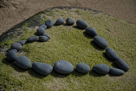 heart made of pebble on a rock photo
