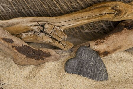 driftwood: single stone heart and driftwood on the beach