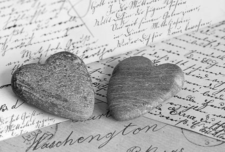 two stone hearts on old handwritten postcards in black and white