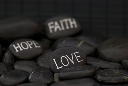 black pebble with engraved message love, faith, hope Stock Photo - 6384257
