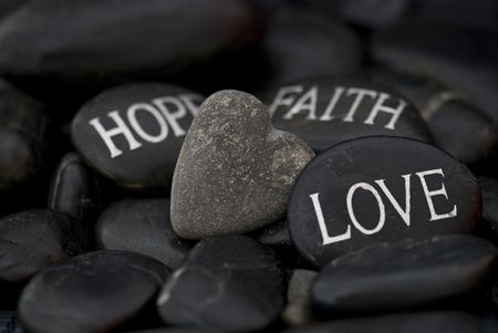 hope: black pebble with engraved message love, faith, hope and stone heart Stock Photo