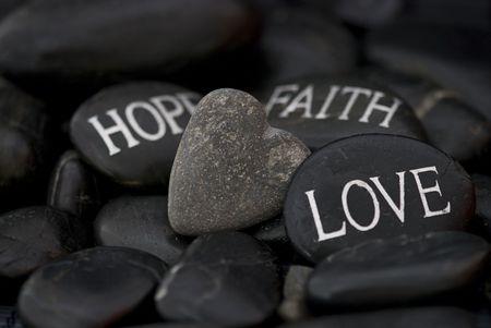 Guijarro negro con corazón de amor, la fe, la esperanza y la piedra de mensaje grabado