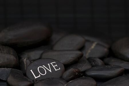 black pebble with engraved message love,  photo