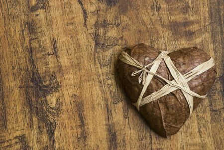 tied up heart on wood background Stock Photo - 6534721