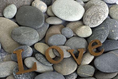 word love in rusty letters on pebble Stock Photo - 6534722