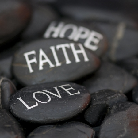 black pebble with engraved message love, faith, hope