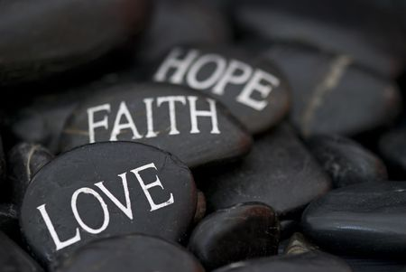 geloof hoop liefde: zwarte kiezel met gegraveerde bericht liefde, geloof, hoop Stockfoto