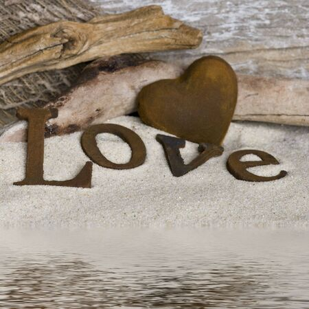 driftwood: word love and heart in sand