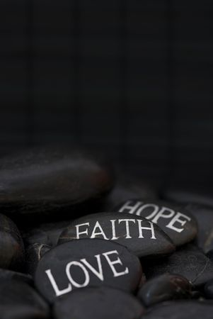black pebble with engraved message love, faith, hope Stock Photo - 6550587