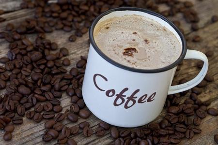 emaille coffee mug on old wood