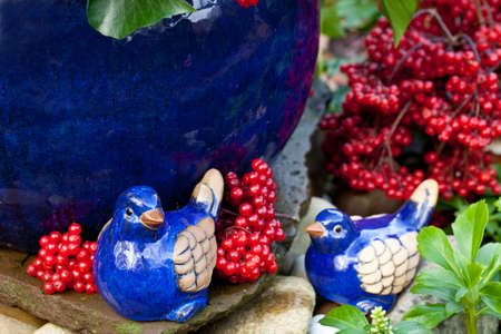 two blue ceramic birds and red berries Stock Photo - 9832278