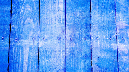 Blue vetical wooden planks with screws on the middle of every plank with cracked paint and some white spots. texture of old wooden planks with cracked and smeared paint
