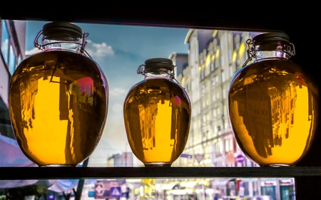 wärmflasche: three round bottles with golden yellow transparent liquid stand on wooden shalved against window with houses cars and people on the street. bottles as decoration of small family restaurant