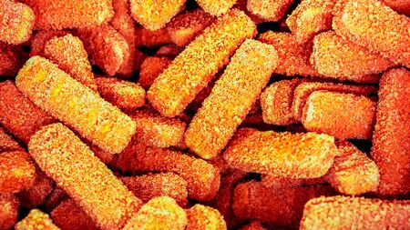 a lot of yellow orange half-finished fish sticks at frozen shop basket as background. half-finished fish sticks as good varient to time-saving cooking Stock Photo