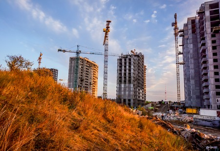 Big future multi-store housing complex with autumn golden yellow grass in sunset sky. Building cranes in front of a multi-storey building under construction which stay one by one
