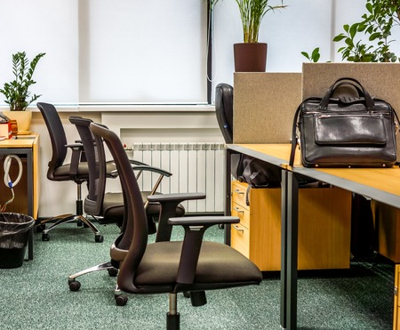 Open workplase with a few black armchairs near brown table with black bag on it against light carpet, flowers on window. Classik office landscape with work atmosphere
