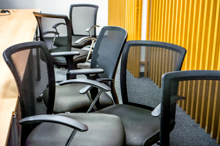 many black office armchairs chaoticly stands one by one against yellow wall with vertical lines. Classic meeting room with black armchairs with grid back after meeting