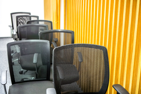 concision: many black office armchairs chaoticly stands one by one against yellow wall with vertical lines. Classic meeting room with black armchairs with grid back after meeting