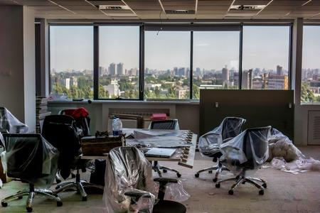 bureau préparant pour le déménagement. les fauteuils de bureau noirs se rangent dans un emballage transparent, les panneaux de réunion sont posés sur la table, une fenêtre sans fleurs et un sol sale comme symbole de la collecte d'objets Banque d'images