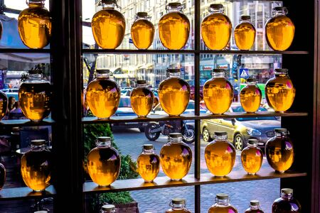 wärmflasche: big and small round bottles with clean yellow orange transparent liquid stand on wooden shalved against big window with street in small family restaurant, fruit compote bottled and placed as a decoration Lizenzfreie Bilder