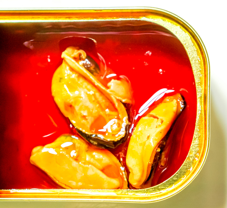 close up of brilliant can with three orange mussels that swimming in redoil against white background. Food Still Life with seafood delicacies. marinated in oil mussels in a can