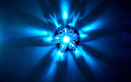 Mystery blue lamp light as big star. Circle chandelier with crystals, round mirror and lamps which made reflection on ceiling as star light. Beautiful luxury chandelier with brilliant and light inside