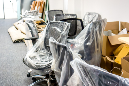 packaging things for office moving. office prepearing for moving. black office armchairs pack into clear package, boxes with documents and carpets laying on the floor as symbol of moving.