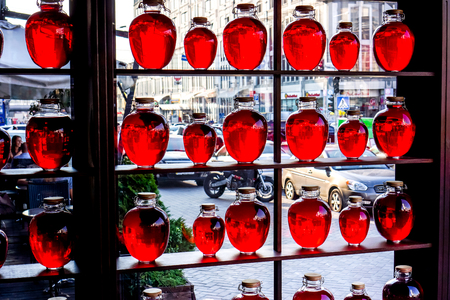 wärmflasche: many different sizes round bottles with red transparent liquid stand on wooden shalved against big window with street in small family restaurant, Red fruit compote bottled and placed as a decoration