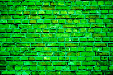 strong emerald green brick wall with cracked parts and white spots as background. Colorful brick wall pattern, painted bricks as urban texture